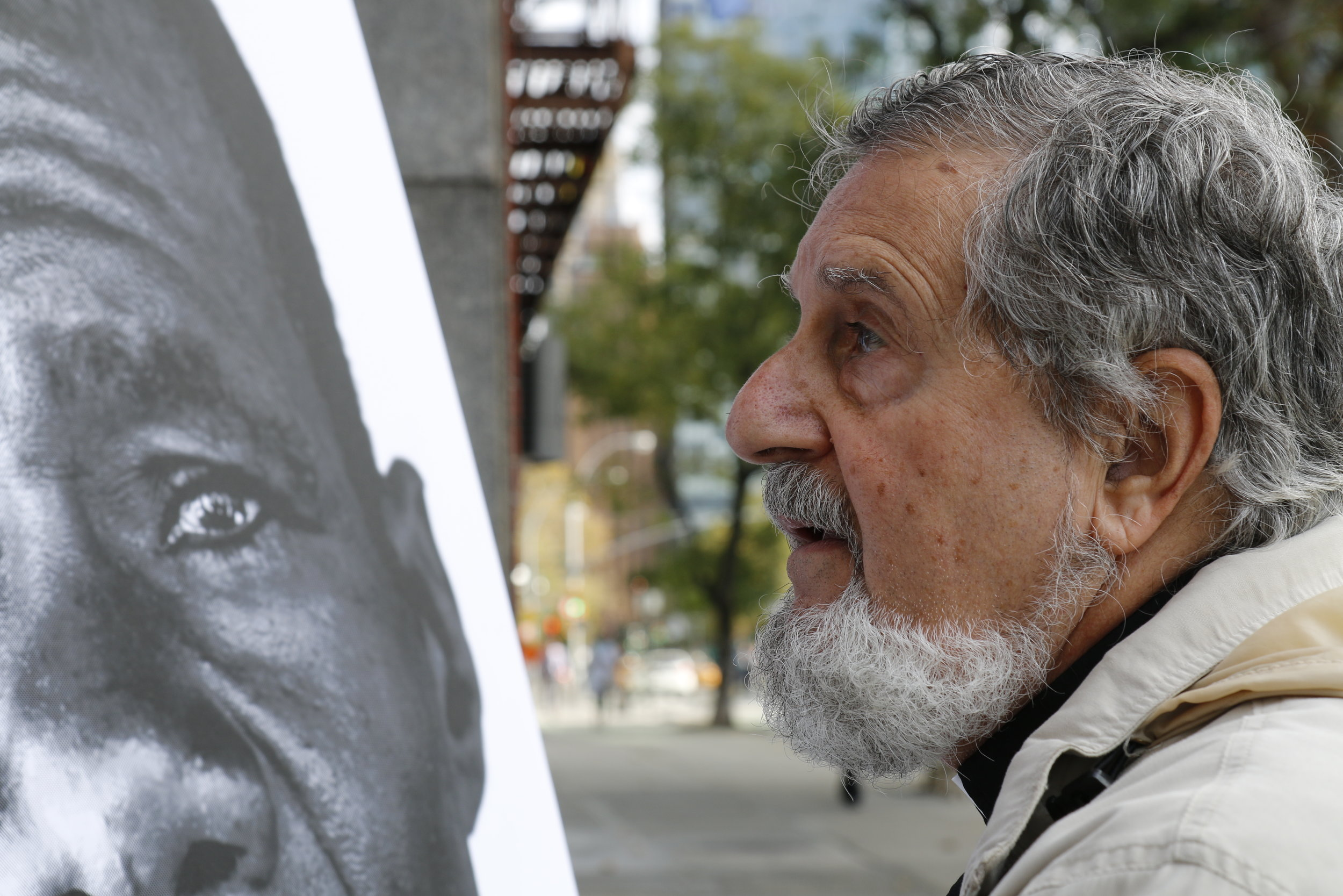 A man examines one of the cholera victim portraits installed by MCC and partners. Bea Lindstrom.