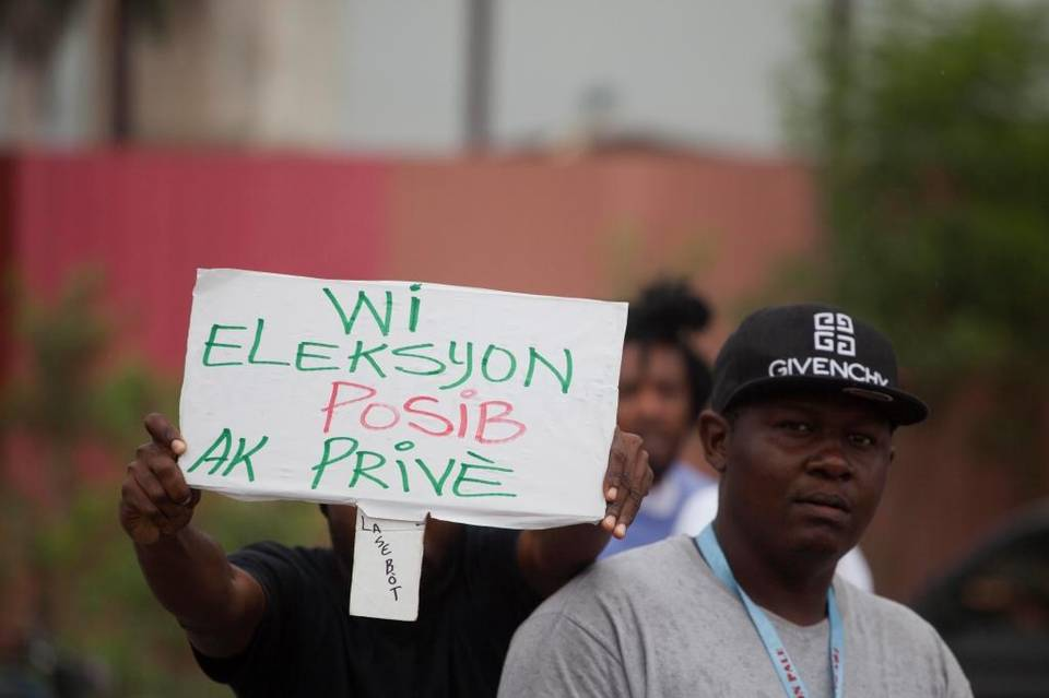 "Photo: Dieu Nalio Chery, AP. A demonstrator holds a sign that reads """"Yes the election is possible with Privert"" from  Miami Herald  article, June 2016"