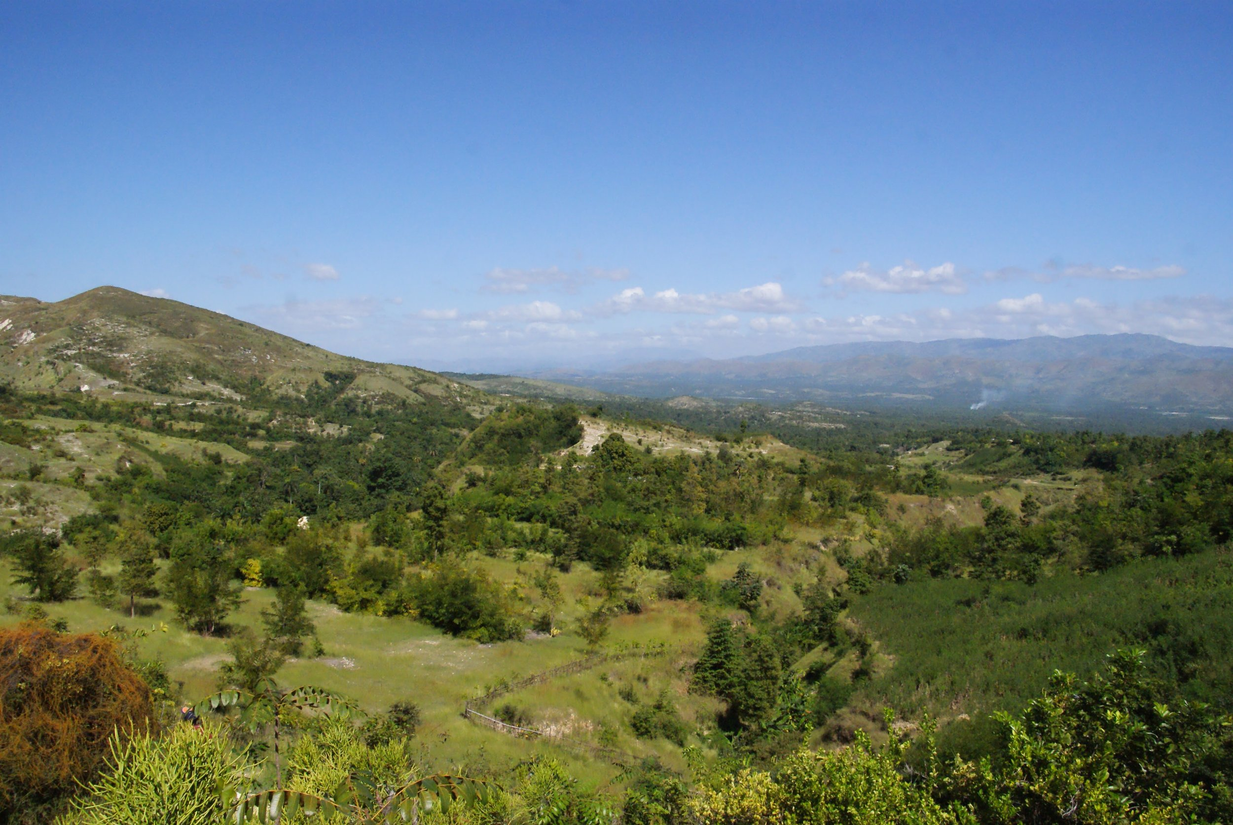 MCC has supported the reforestation work in the Artibonite Valley that is visible in the middle of this photo. Prior to reforestation, agro-forestry and micro-forestry work, the mountainside was as bare as the mountain in the upper left of the photo. Photo credit: Tina Schrag