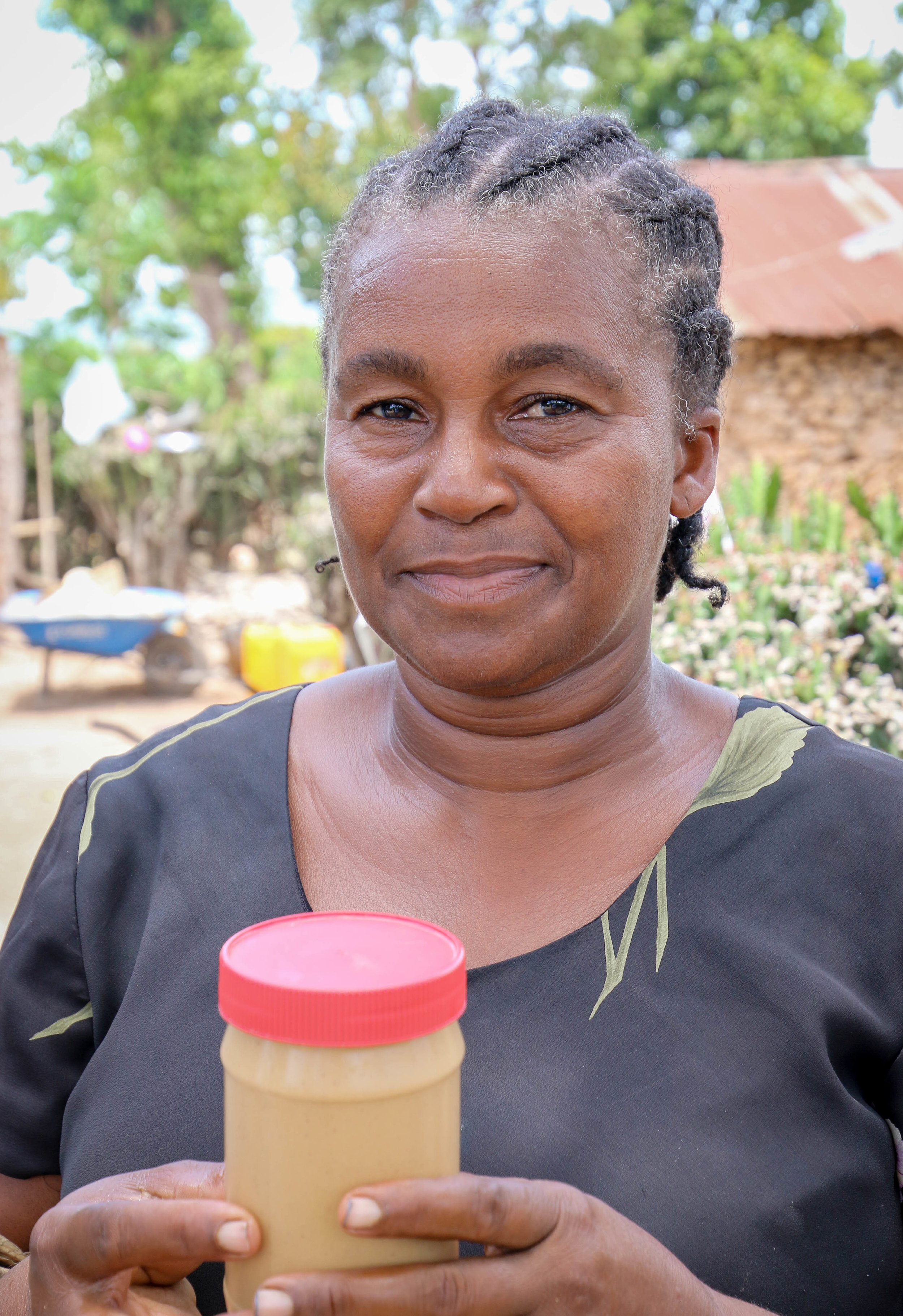 Estann Annyias, President of MCC supported peanut butter making co-op holding of jar of Haitian Mamba, peanut butter. Boyaha, Haiti.