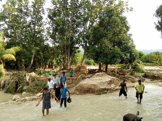 MCC's assessment team wading through a flooded river in the community of Otovan after Hurricane Irma.