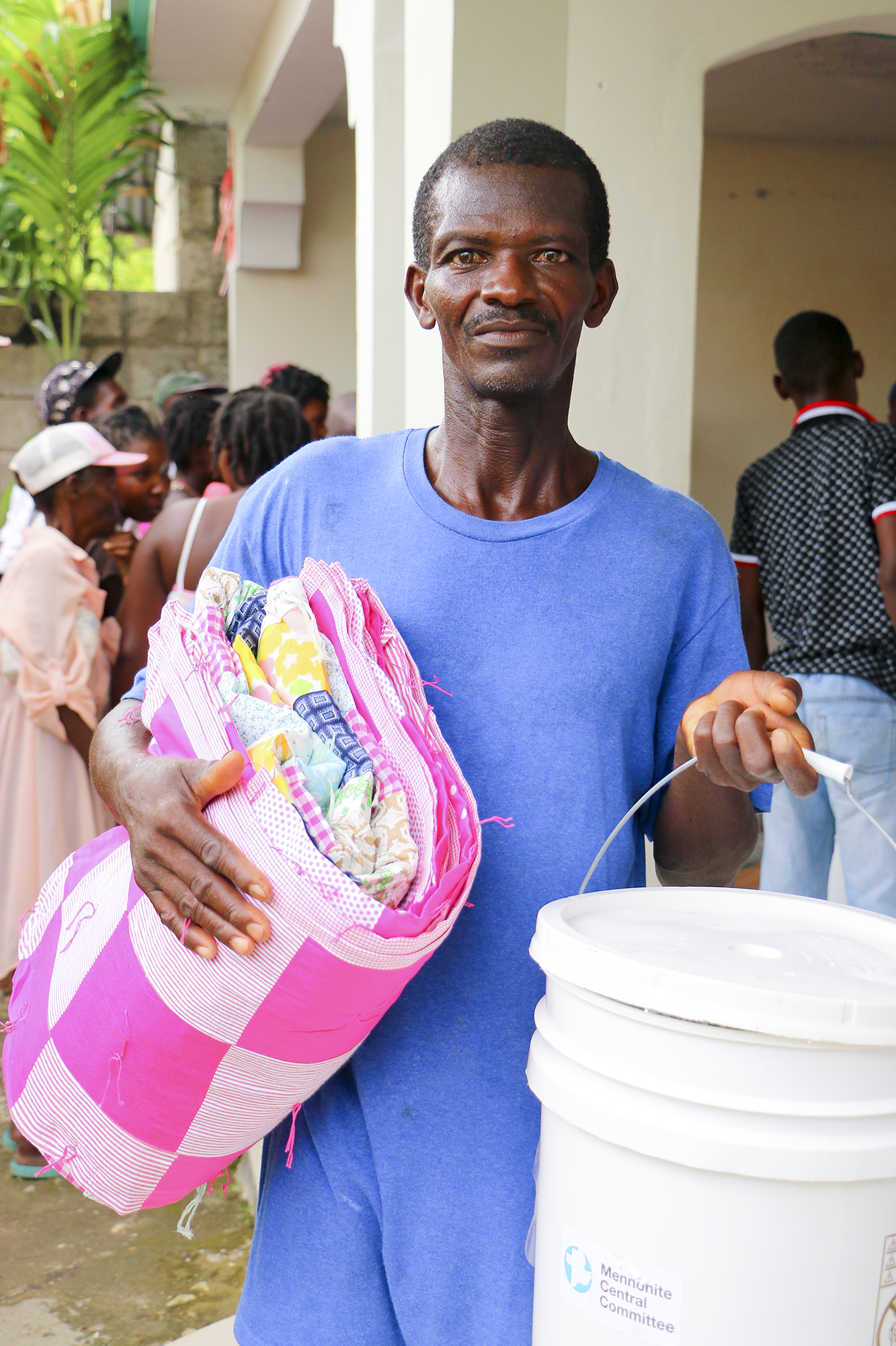 Osa Jonmarits receives material aid from MCC at a distribution point in the town of La Chapelle the next day. MCC material aid included comforters, an MCC relief bucket, and water purification tablets. Photo/Annalee Giesbrecht