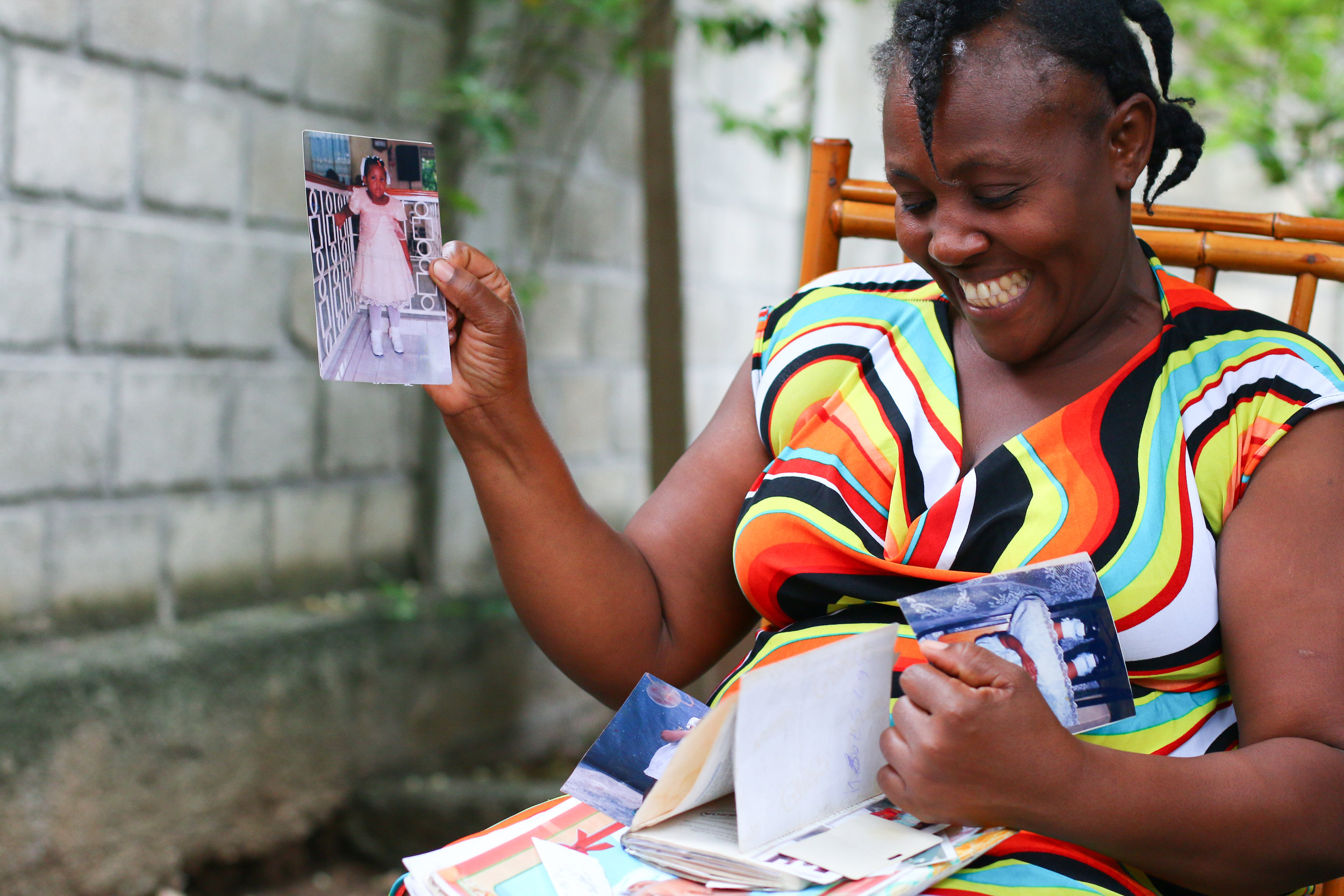 Carline Vilneuve shows MCC staff a photo of her daughter at the SOFA office in Port-au-Prince.