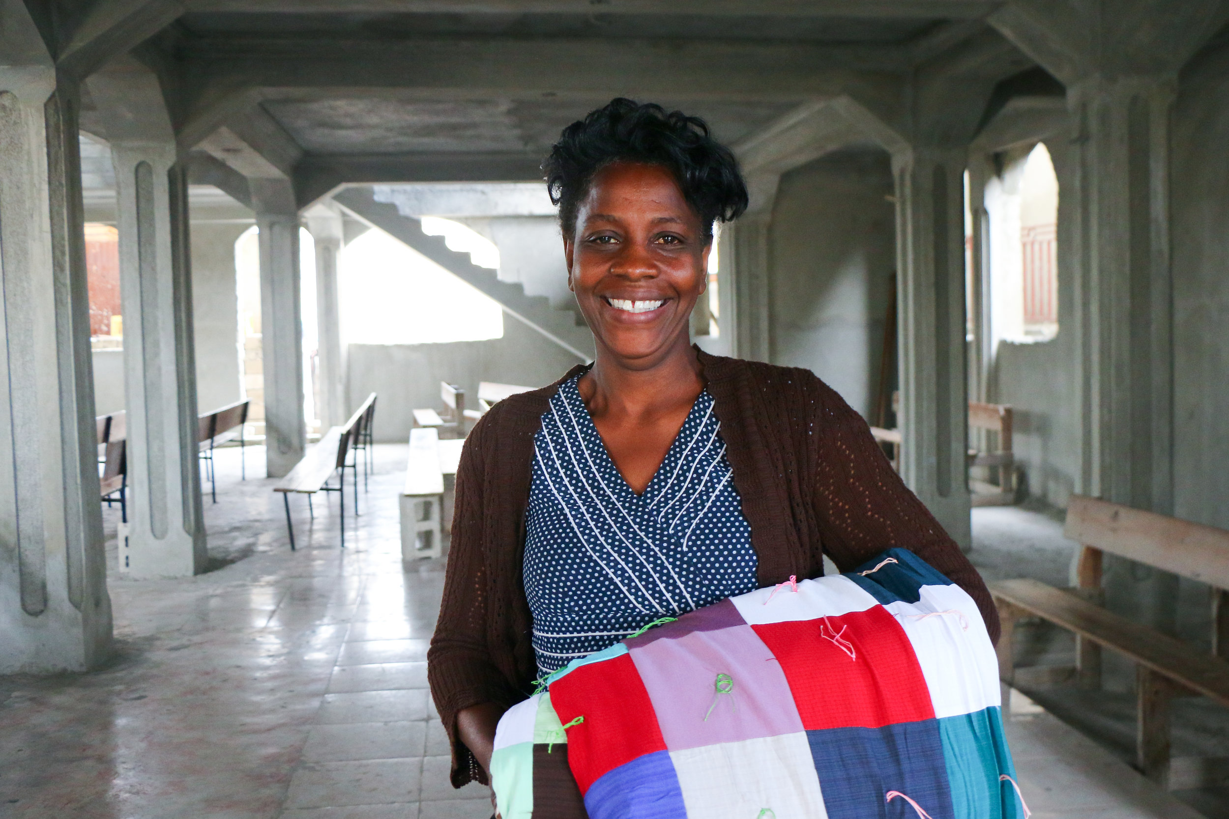 Rosemonde Joseph receives a relief bucket and comforter as part of an MCC distribution in response to the fire in the Boulard neighborhood of Port-au-Prince.