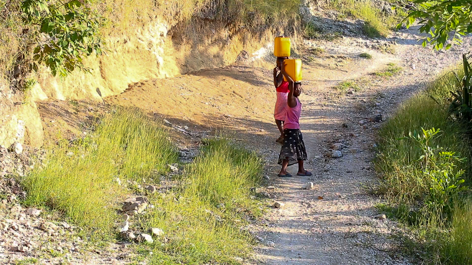 Young girls carry water on the road to Wopisa, a remote community in Haiti's Artibonite department.
