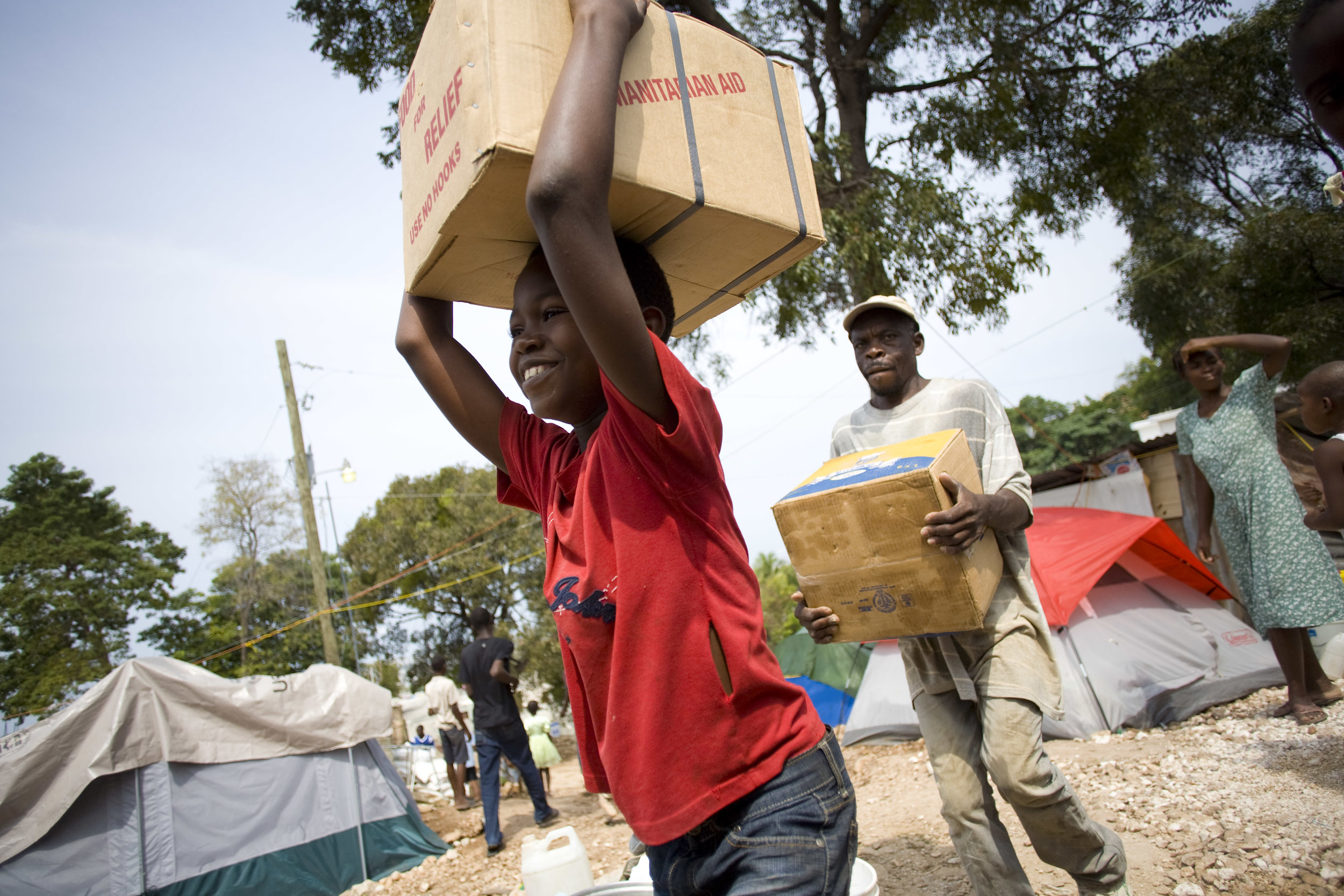 For immediate response, MCC provided canned meat and material aid to local communities. Nicholas Mardoche, pictured above, carries a case of canned meat from a delivery truck to a storehouse in the camp where he lived.