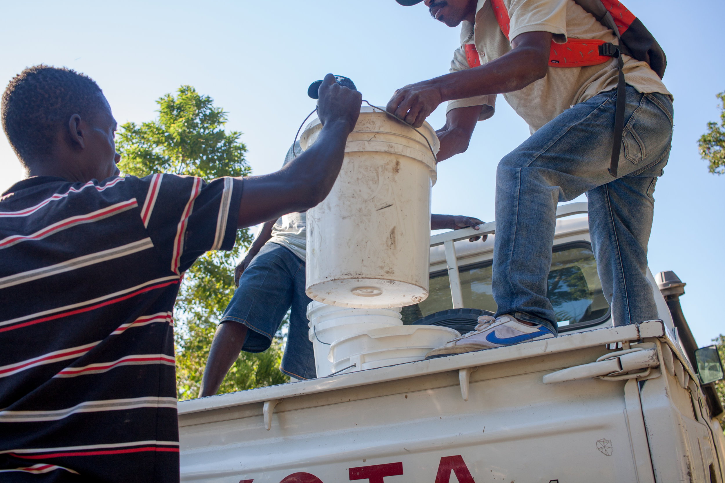 Residents of Bingo help unload relief buckets from the MCC pickup. MCC Photo/Annalee Giesbrecht