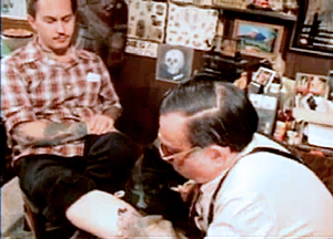 """Film still from """"Stoney Knows How"""" of Stoney tattooing the Legendary tattooist Don Ed Hardy (1980)"""