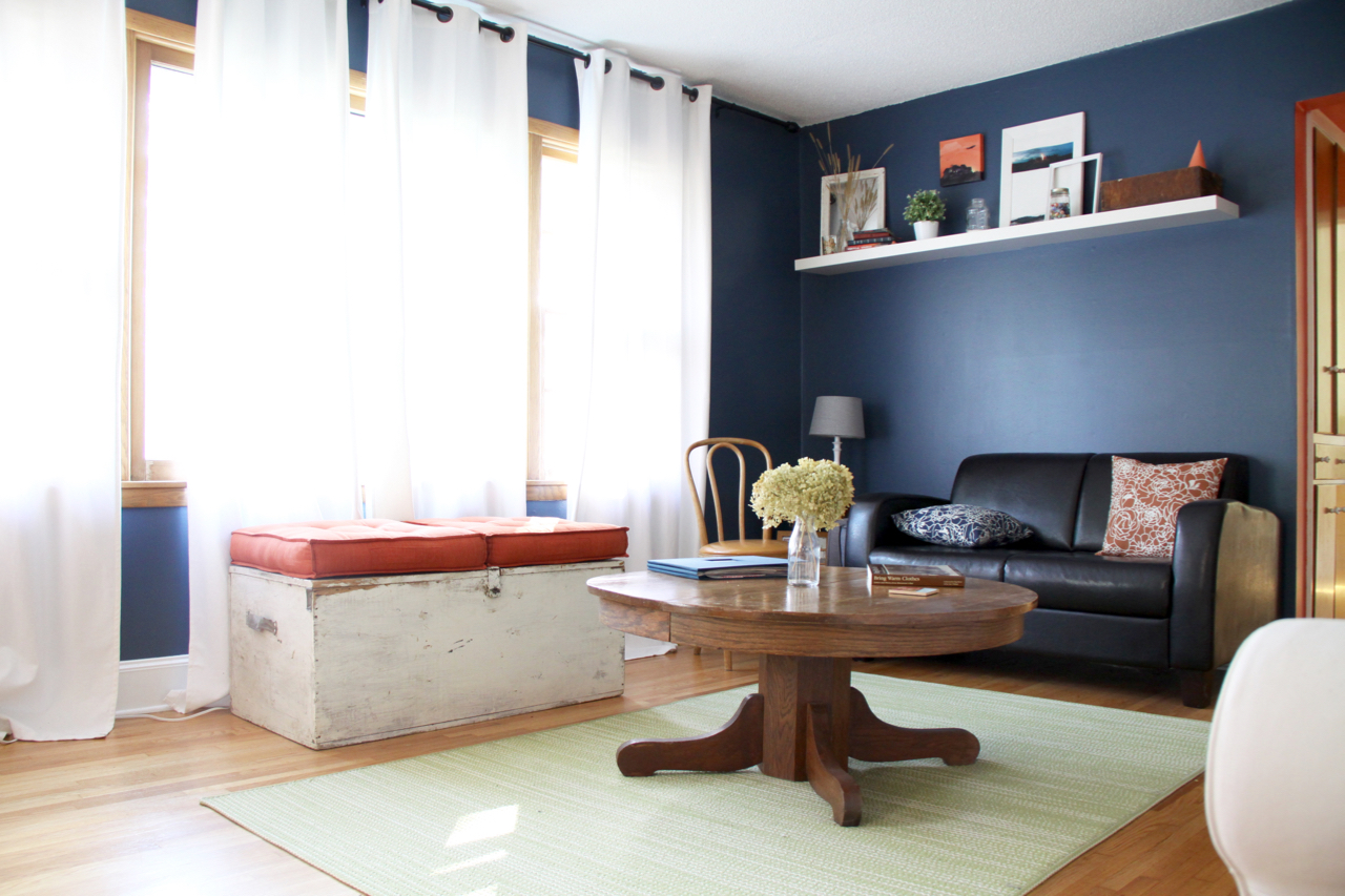Living Room with Blue Walls, White Curtains, Leather Couch