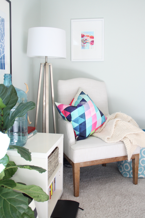 Geometric Pillow and Colorful Artwork in Bedroom Reading Corner