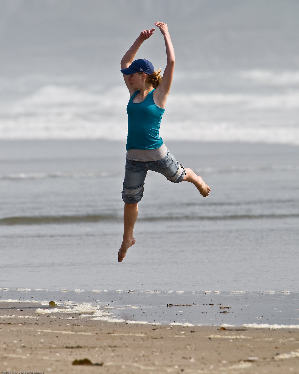 Girl dances at water's edge on Morro Strand State Beach