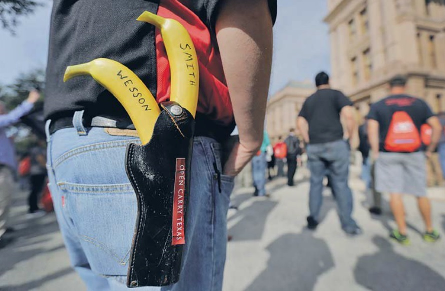 """Jason Greene locked and loaded with a pair of bananas marked """"Smith"""" and """"Wesson"""" at a rally in support of open carry laws in Texas in 2015. AP/Eric Gay"""