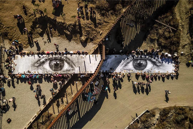 "An installation at the wall between the USA and Mexico, by French artist JR. ""Giant Picnic"" was a long table featuring two eyes — described by the artist as the ""eye of a dreamer [with] people eating the same food, sharing the same water, enjoying the same music.""  Except the project was illegal on the US side — which is why half of the people were sitting on the dirt. Photo: Public Radio International."
