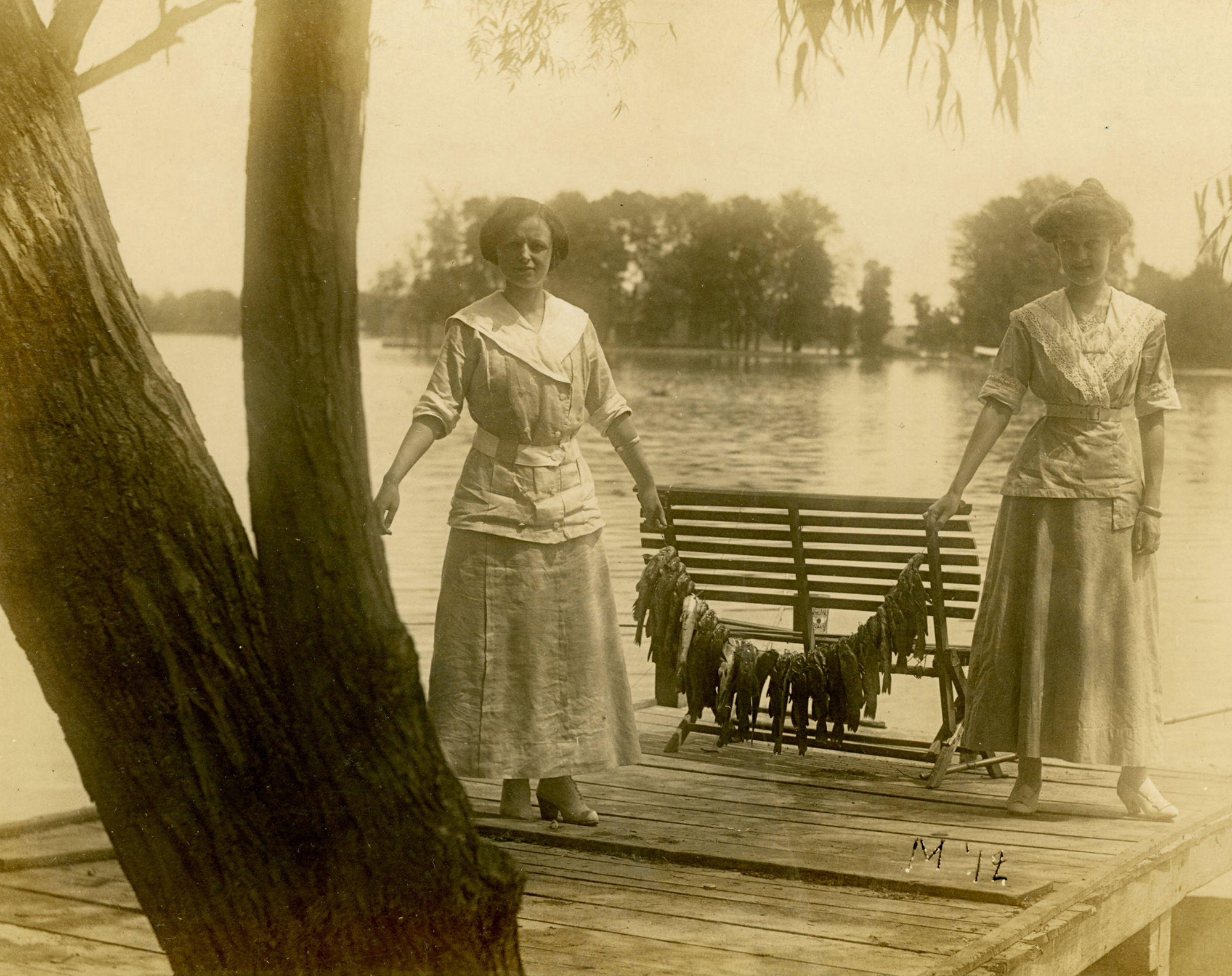 Real photo postcard of women holding a string of fish, 1912