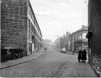 THE R.E.A.L. on left with Anscombes grocery shop on the corner of Lees Street and Tommy Harpers Bookies shop with two ladies talking outside.