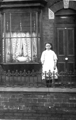 Tonys mom standing outside 52 James Turner St in 1916. where the family lived before moving to 76 Eva Road. She was the sixteenth in the Haywood family. Photograph from Tony Warrington