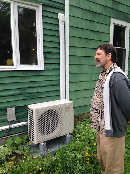 HeatSmart director Jonathan Comstock next to an air-source heat pump compressor unit. Credit: Karim Beers