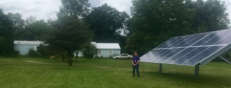 Gail with her ground-mounted solar system in front of her house.