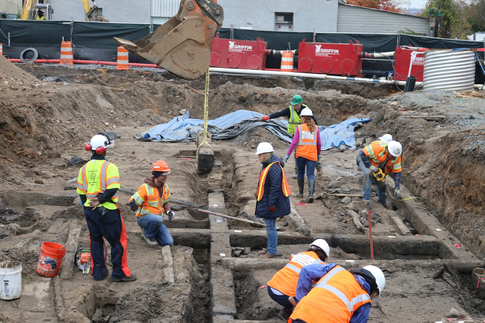 Our archeologists assisted City of Alexandria archeologists and conservators from the MAC Laboratory with removing the remnants of the warehouse for preservation. After the beams were cut into 12 foot sections, they were lifted with a backhoe onto a flatbed trailer for transport.