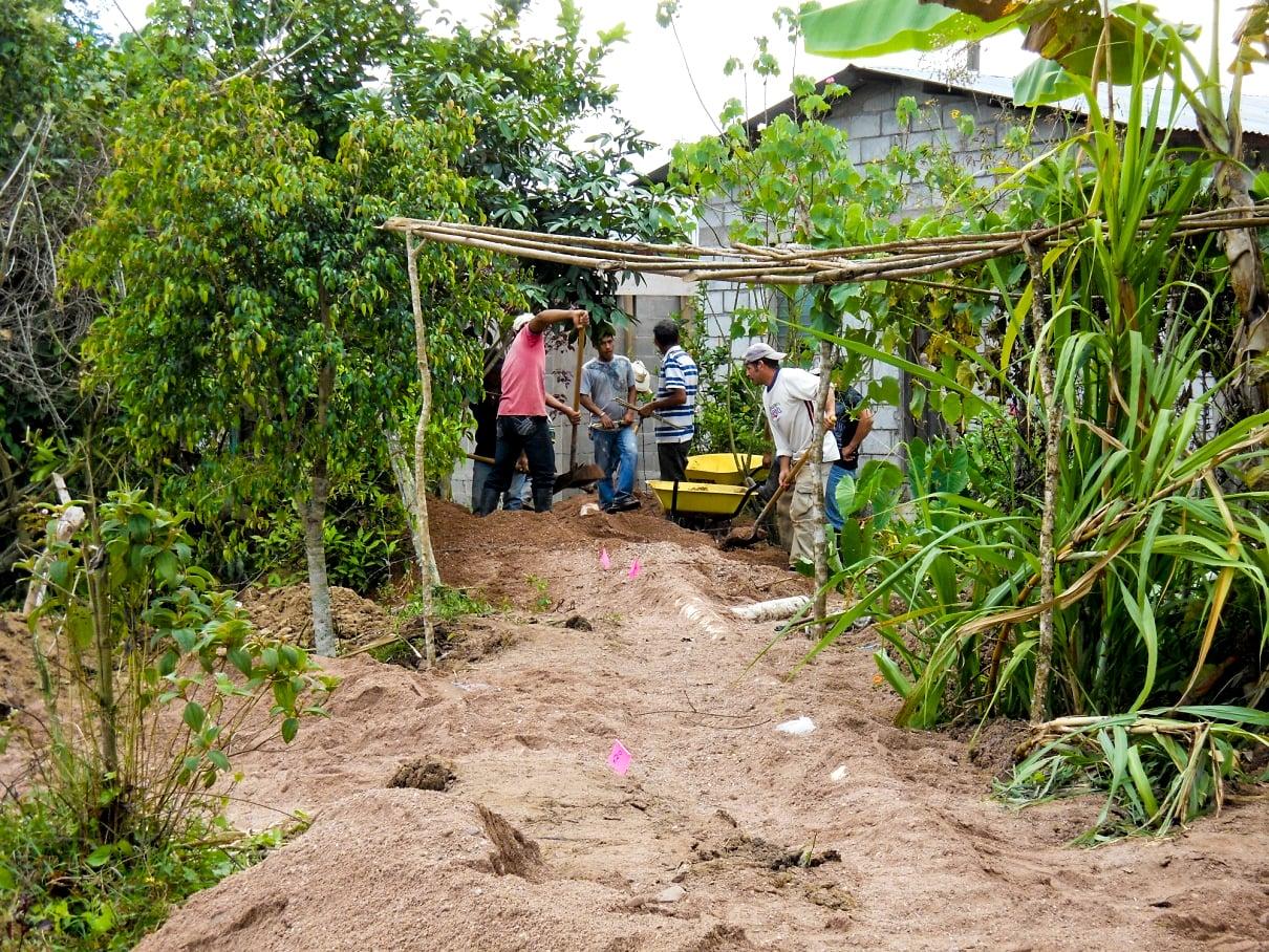Dulce Vivir workers laying sewer line through backyards.