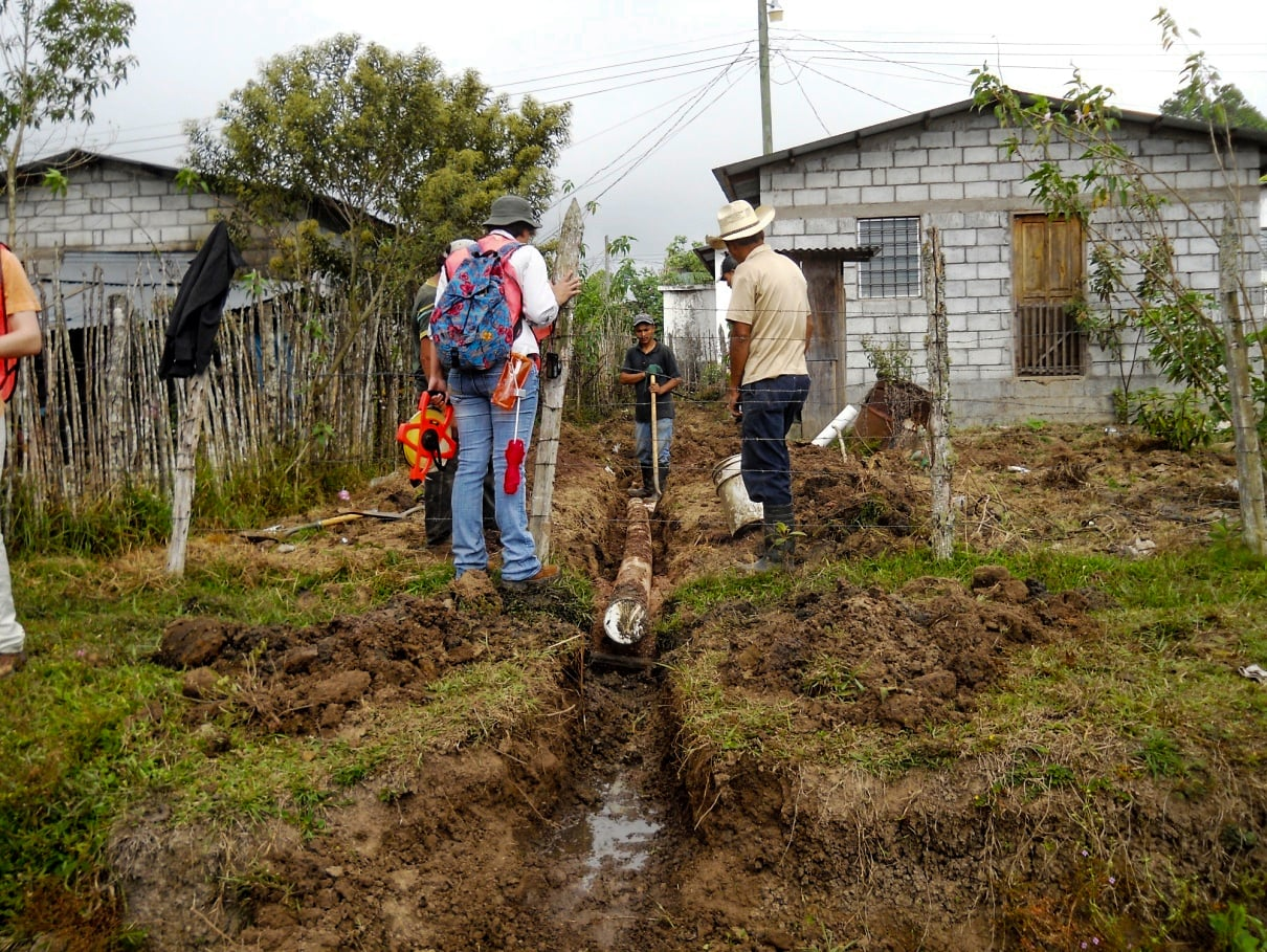 EWB member Ruth Castillo laying out sewer line with Honduran workers.