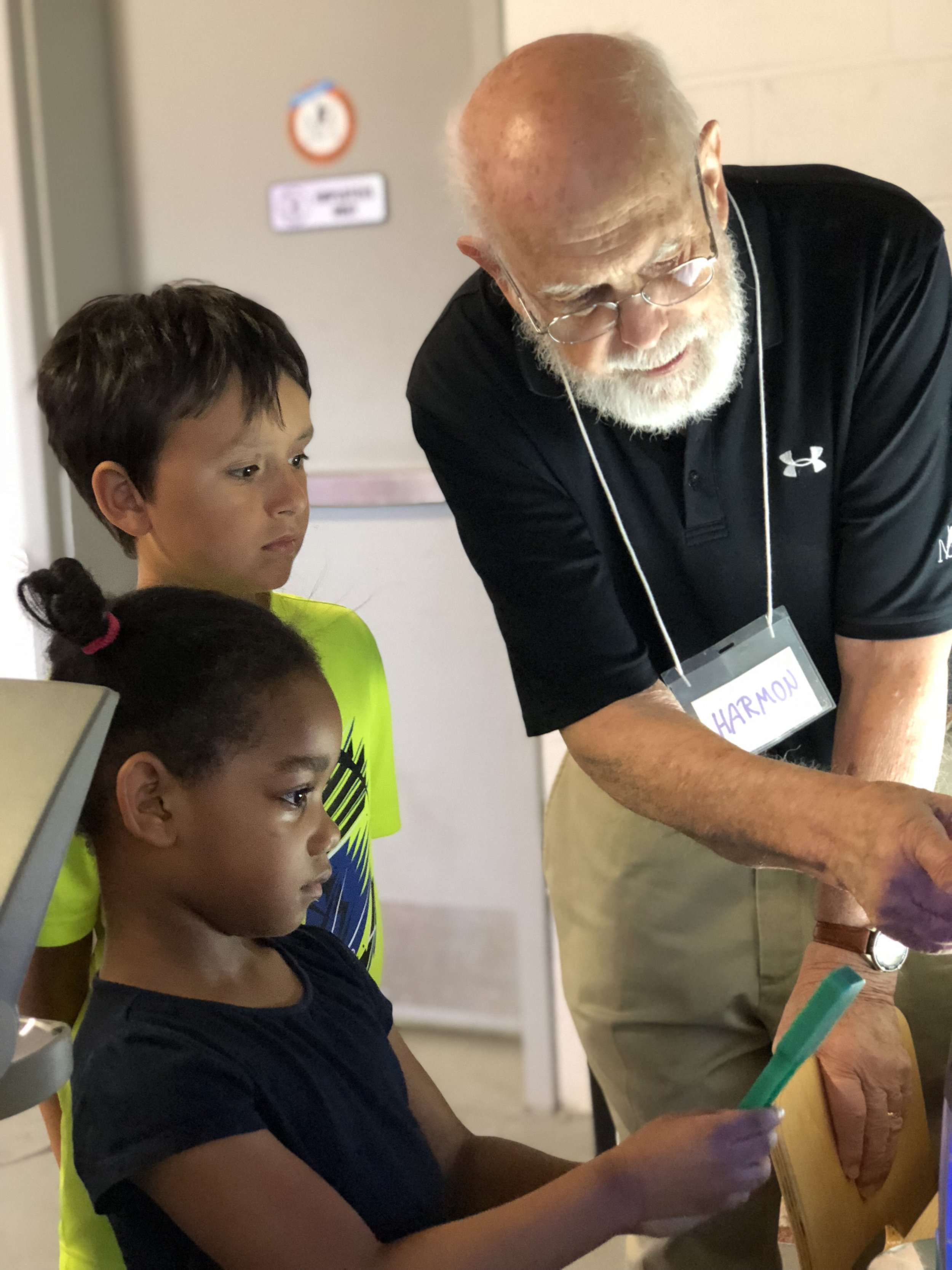 A Museum volunteer works with children on a filtered light project during Science Sunday.