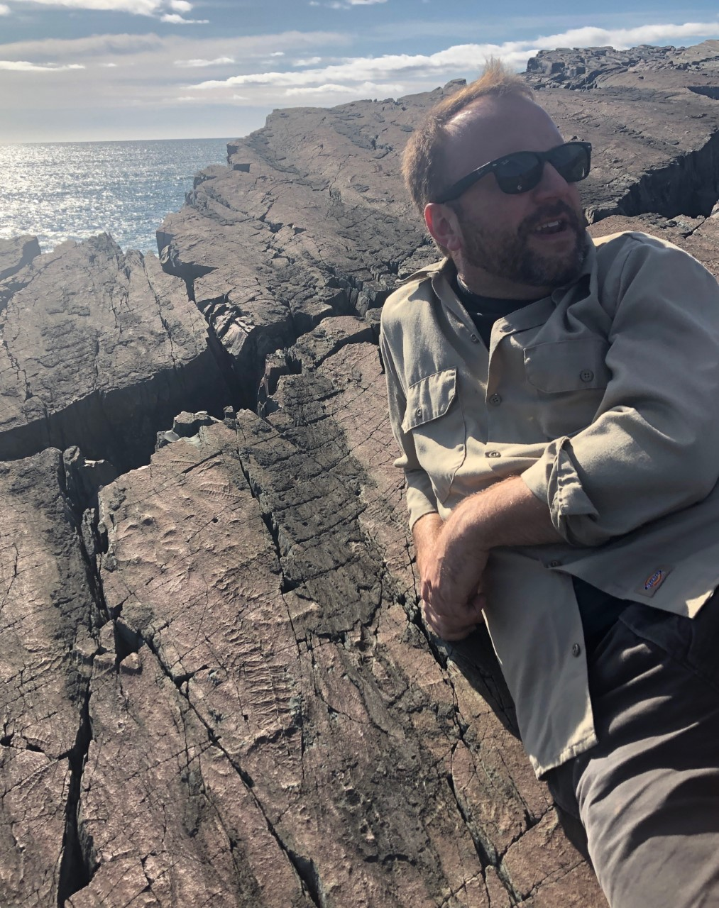 I'm relaxing on a 560 million year old cliff over the Atlantic Ocean at Mistaken Point Ecological Reserve, a UNESCO site. Next to me are fossils molds from some of the earliest known living organisms on our planet!