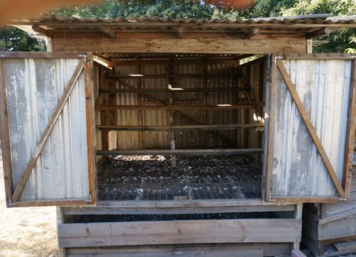 The PoopCoop! This coop was my idea, designed and built by tonia. It has a 1x2 inch galvanized wire mesh floor and a wooden subfloor. The subfloor is well ventilated and can be accessed for poo removal from the front and back. There are boards screwed on the access points to keep the chickens from getting in there scratching around for bugs. I would make the access slots a little taller for easier access, maybe with doors instead of boards screwed on. Otherwise, it works pretty great. Make sure you orient the wire and the boards on the drying floor in the right direction for easy scrapping, otherwise you get a washboard effect.