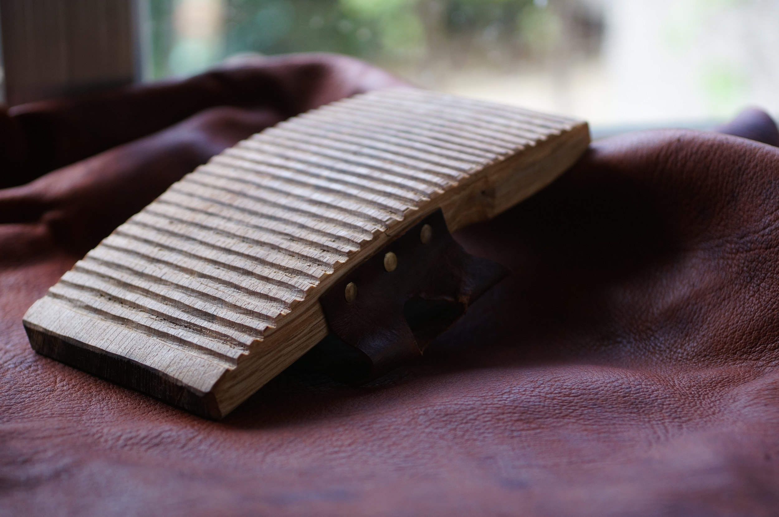 Graining board for softening and raising the grain of leather.