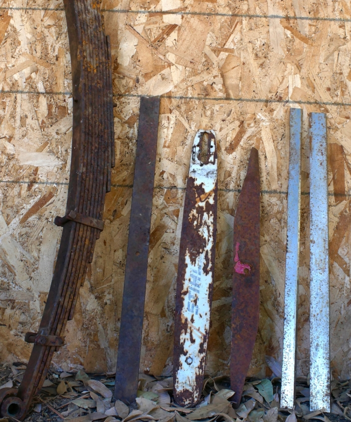 Miscellaneous steel items that could be used to make a tanner's knife. Left to right, a set of car leaf springs, section of leaf spring, chainsaw bar, lawnmower blade, planer blades