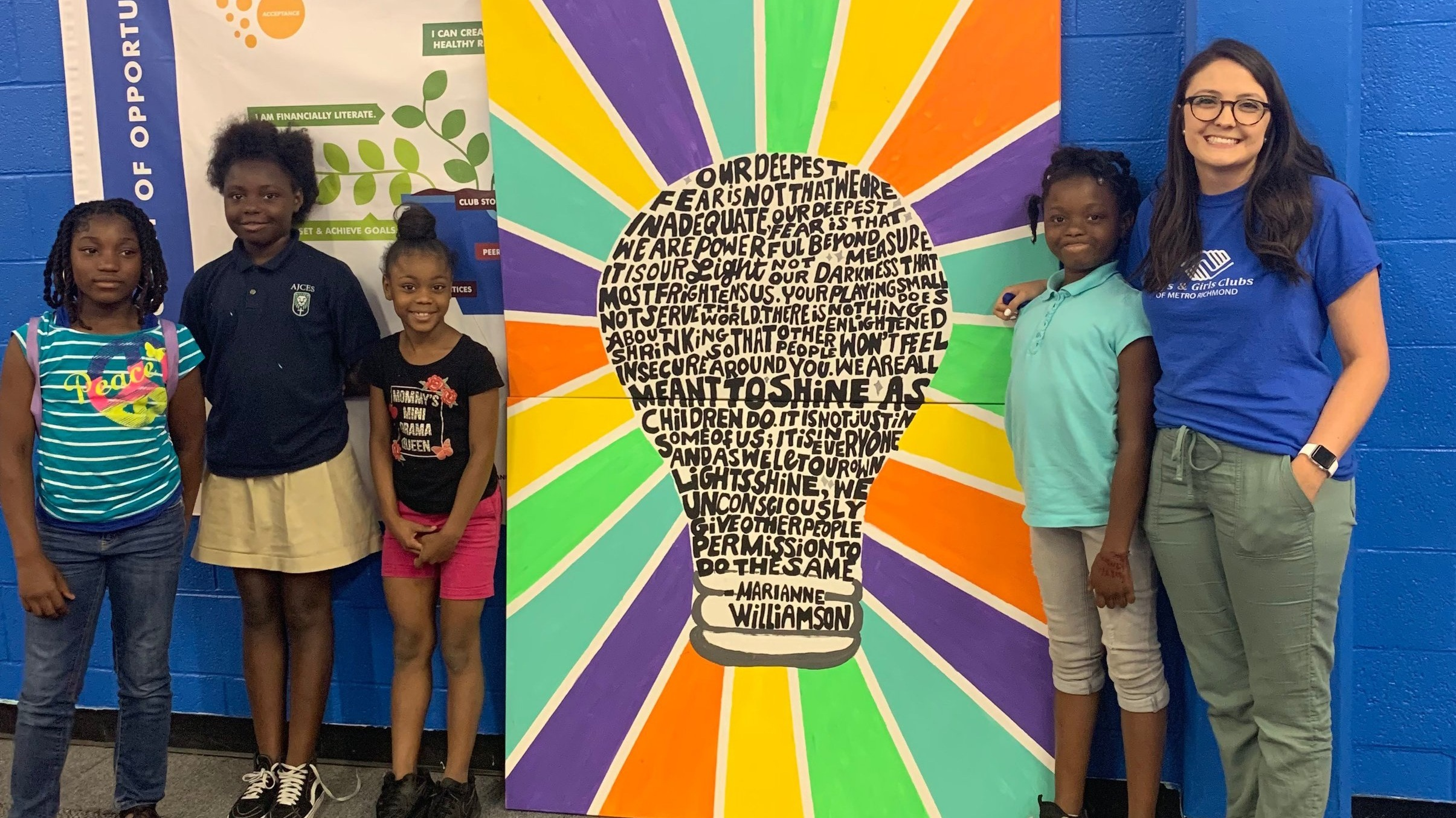 Members of the 1,000 Words interest club and Ms. Abby stand with their finished mural