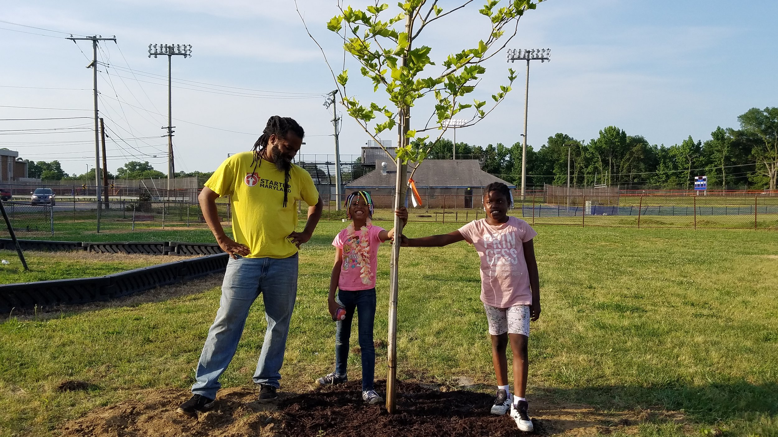 Duron Chavis stands with two proud members after they planted their first tree.
