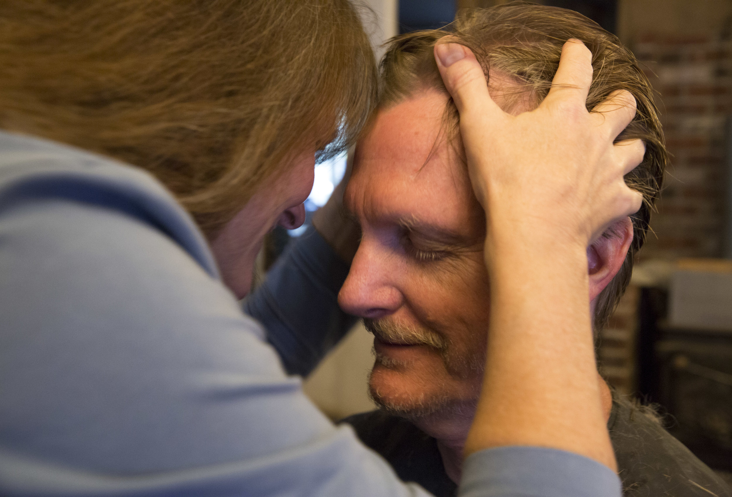 Lorian Moore and her husband, Rex Rohrer, share an intimate moment while she massages his forehead before he leaves for work.