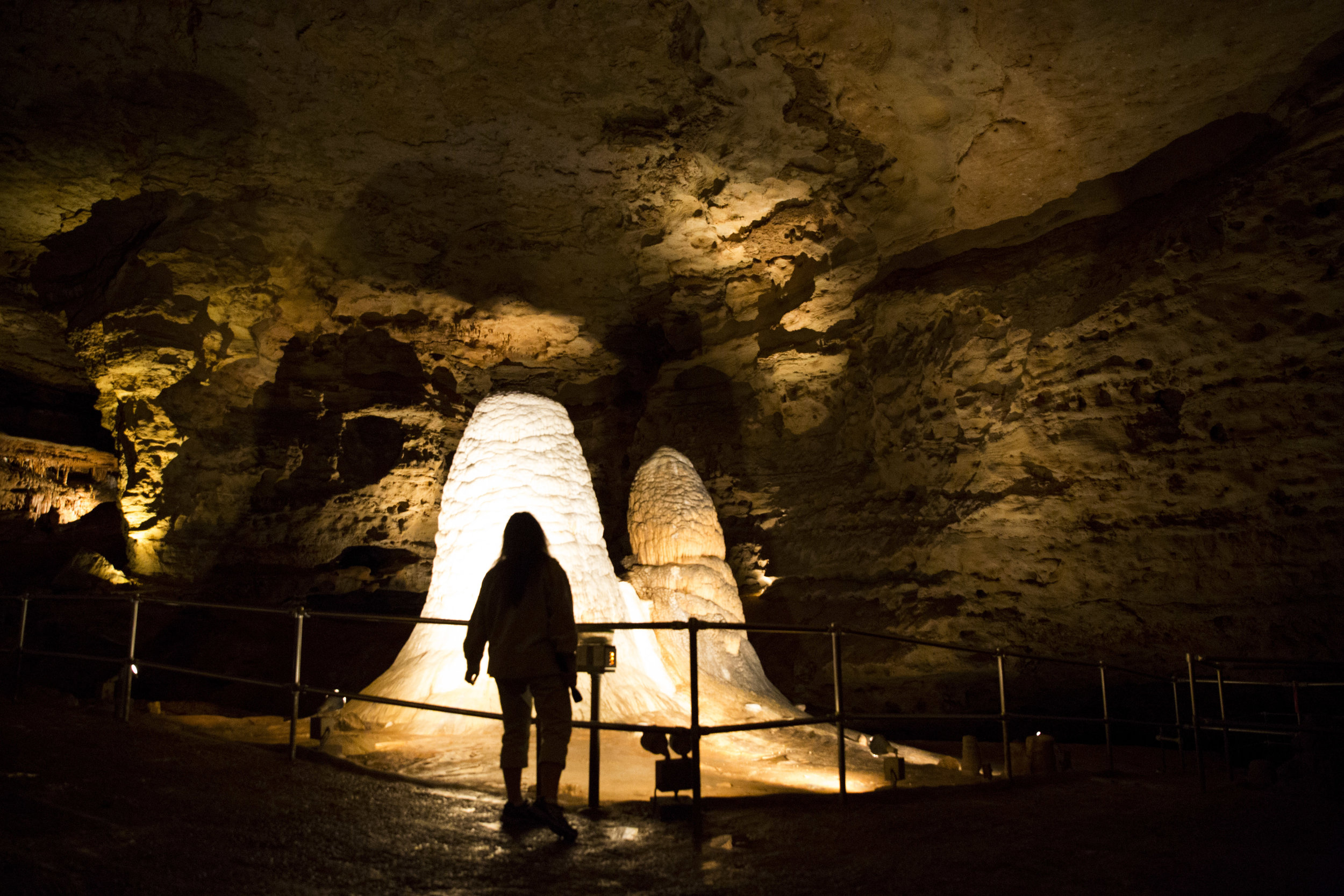 """Lorian Moore, who works at the Onondaga Caves State Park stands in front of the approximately 500,000-year-old stalactites called """"The Twins."""" She works at the park two days a week giving tours and organizing events for Onondaga Friends Association, which is the park's non-profit organization that she helped establish."""