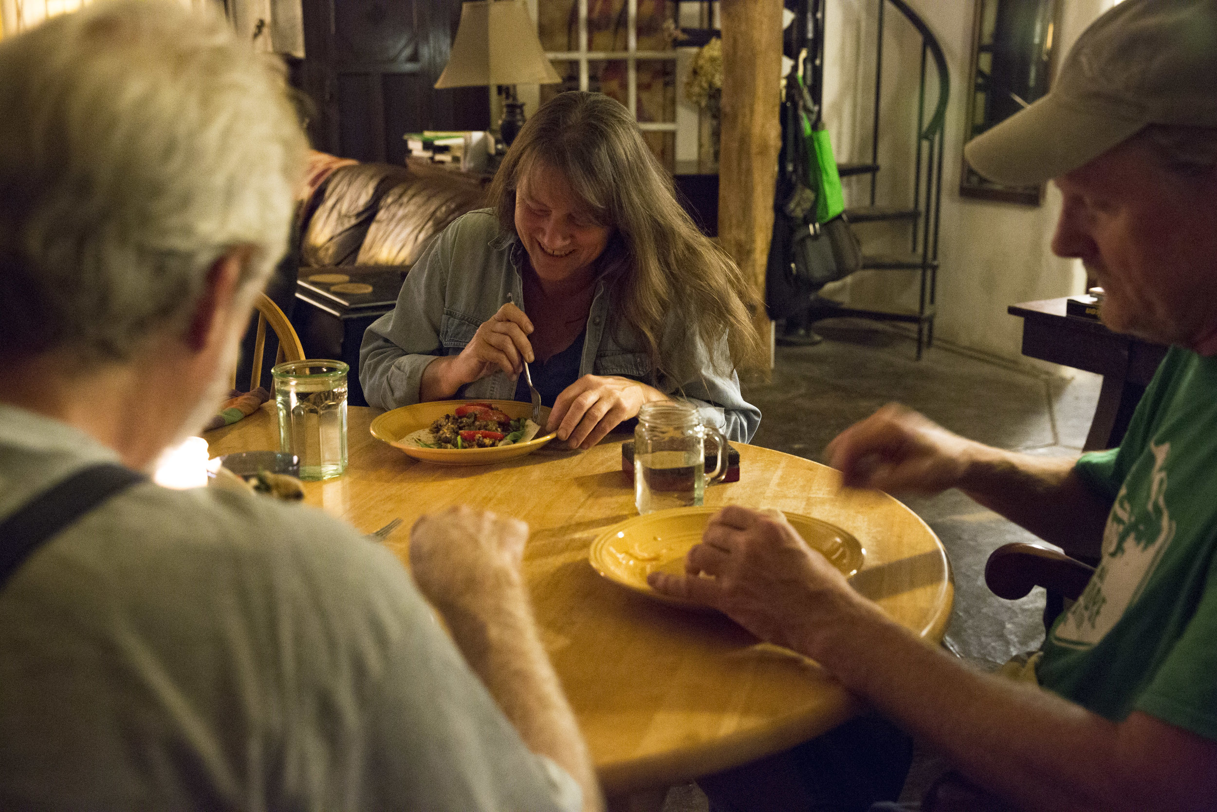 Lorian Moore eats dinner in her living room with her husband Rex Rohrer (right) and their friend Barry Bookout (left).