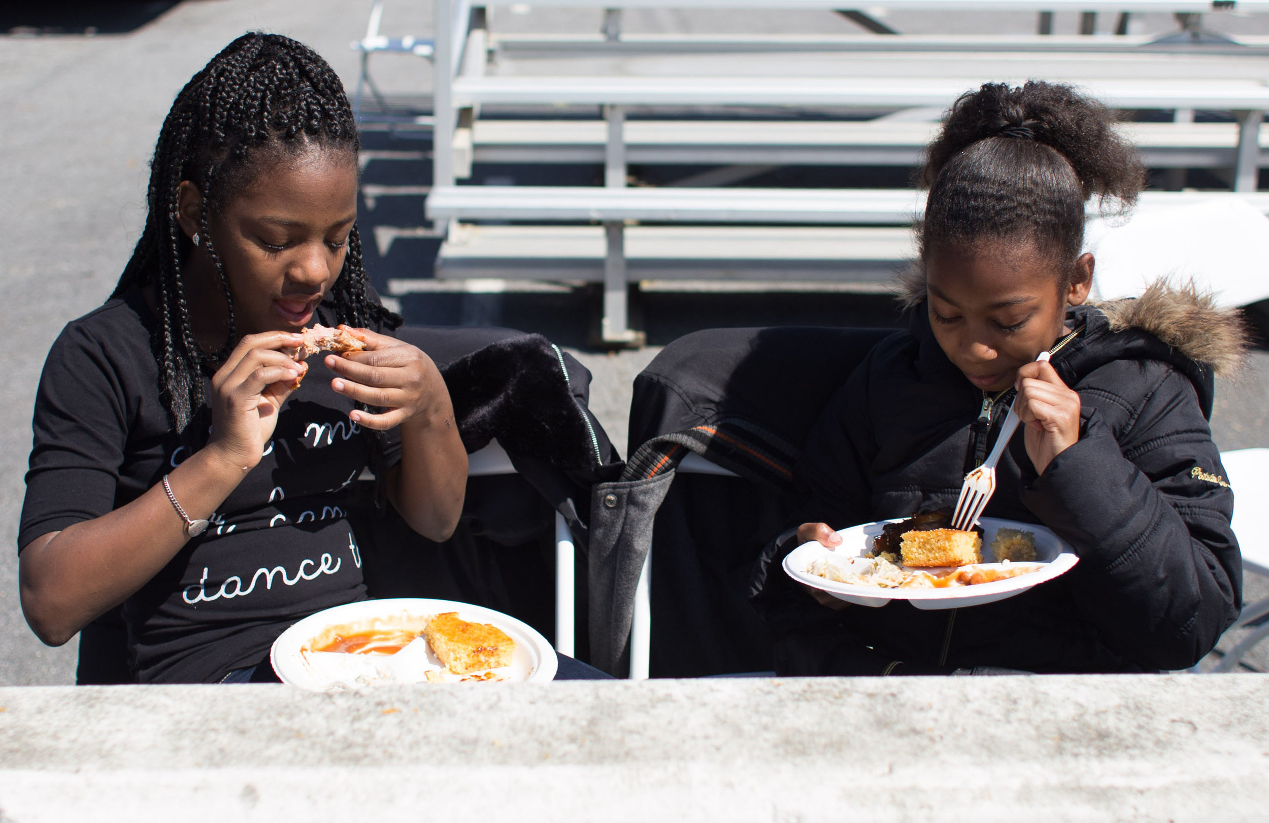 Shani (11) and Shanye Harris (10) eat lunch at the San Francisco's 31st bus road-eo where bus operators compete in a series of driving and safety test including an obstacle course showcasing the drivers best skills at Cow Palace Saturday, April 2, 2016. (Emma Chiang/Special to S.F. Examiner)