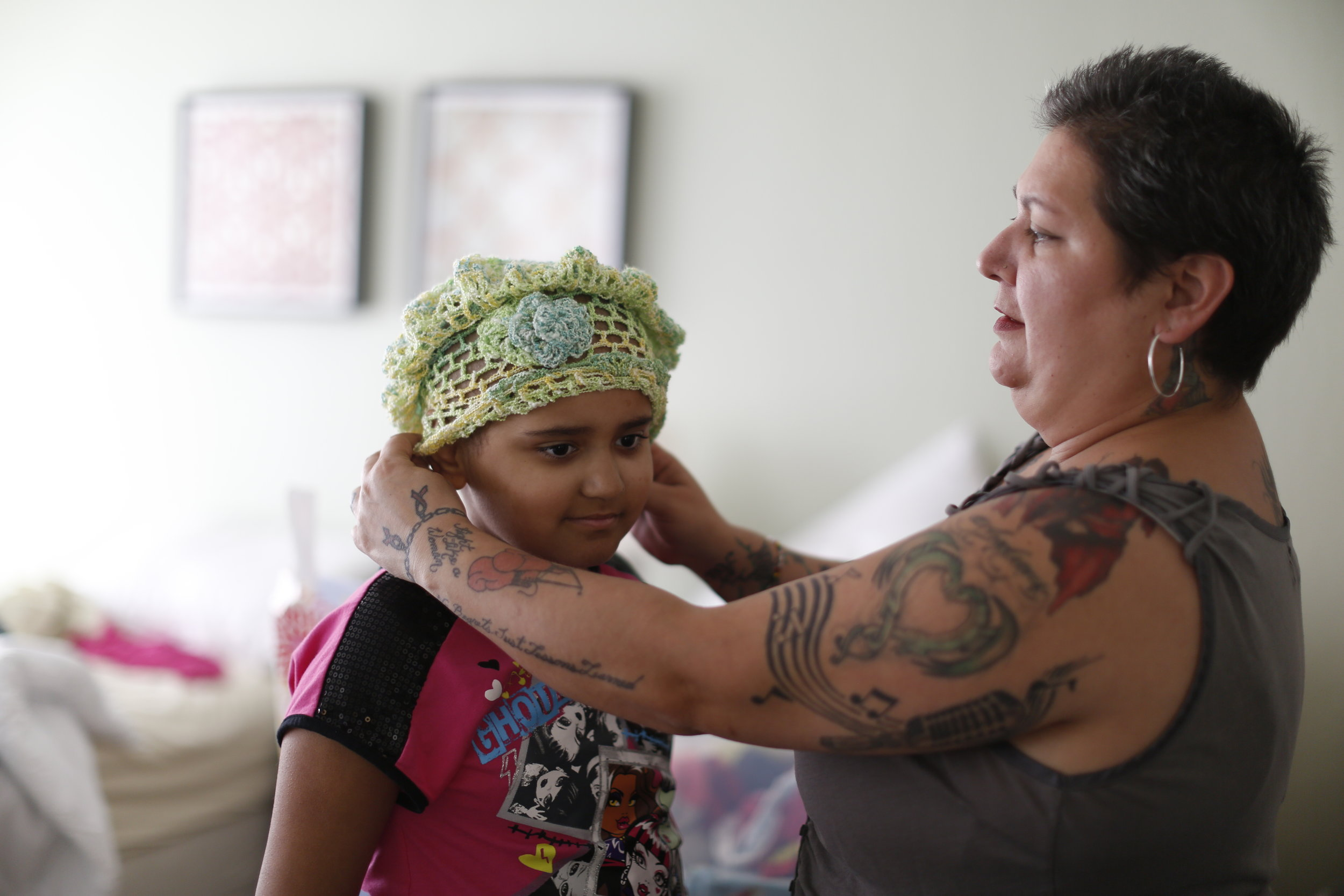Ava Ramirez's, 9, mother puts a kitted hat on her head in their room at Family House, a free home for families of children undergoing long-term care for life-threatening illnesses in San Francisco Calif. Friday April 15, 2016.