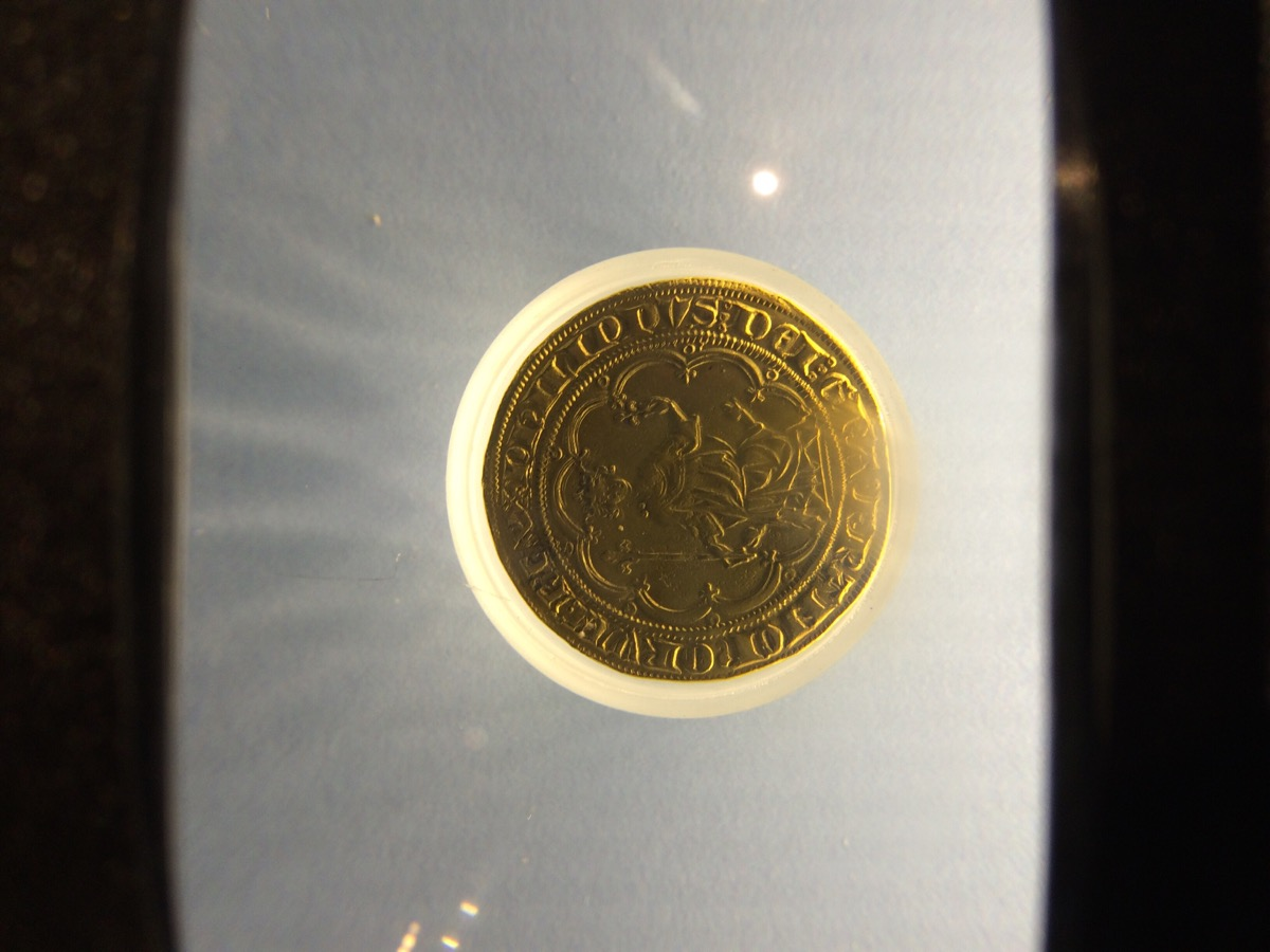 Old Parisian coin under a magnifying glass