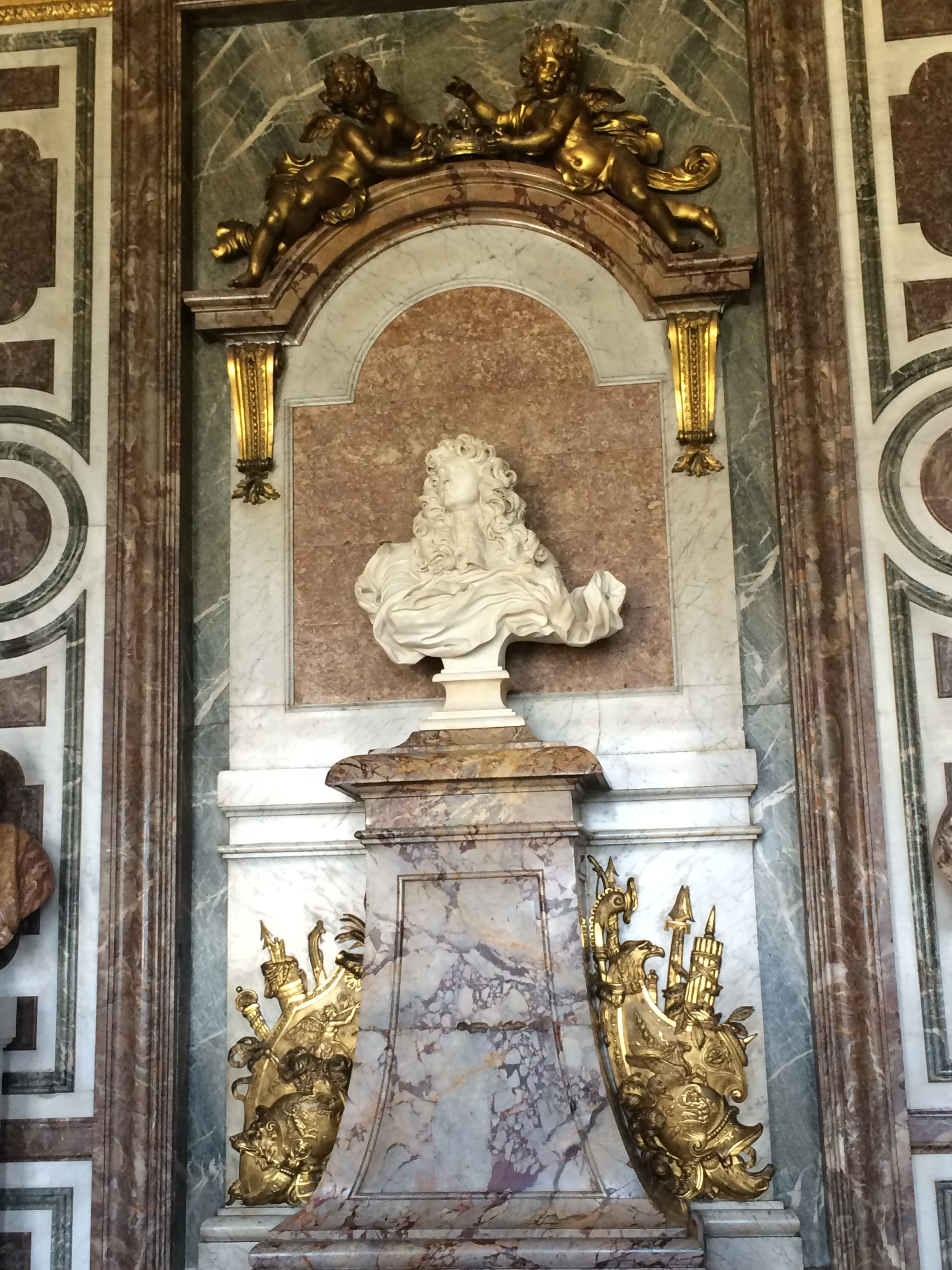 A classically-inspired white marble bust of Louis XIV, sitting on a colored marble pedestal, with gold armor, weapons, and animals protecting him at the base while gold angels lower a gold grown onto his hair as it blows in triumphant, imaginary wind.