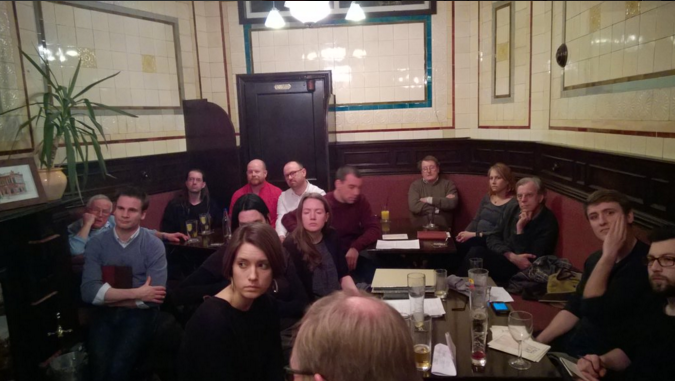 Printing historians and practitioners listen in as Jo Krawec presents her research in the smoke room of the Woodman Pub.