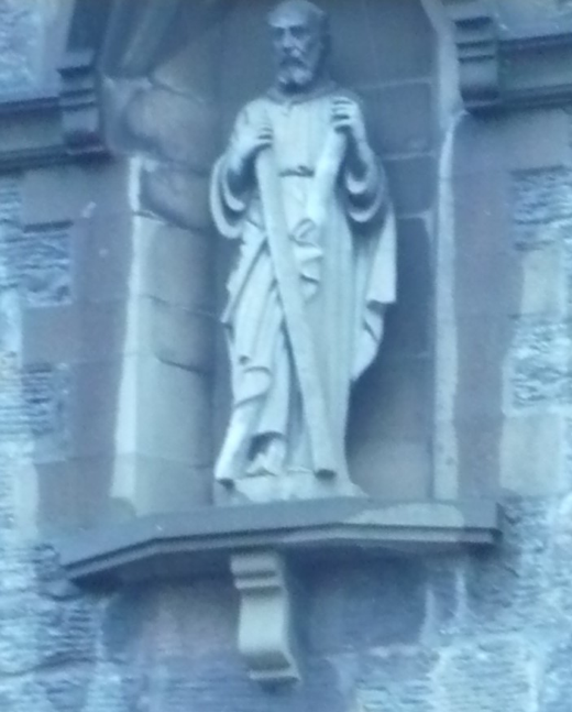 The architectural features of this Arts & Crafts style building include a statue of St Andrew with his satire cross