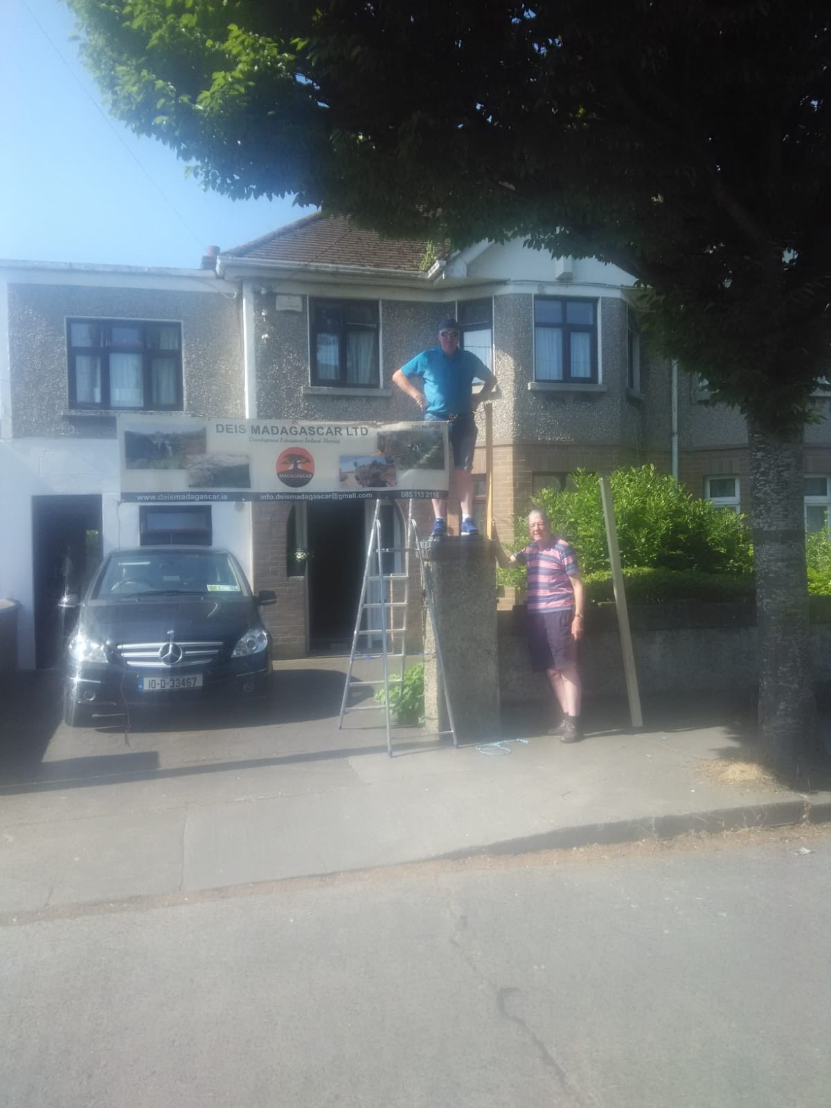 Noel Mooney and helper erecting the  DEIS MADAGASCAR  banner outside of Bernard and Marie's house on Saturday last  in preparation for coffee morning and cake sale.