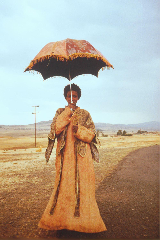 Young deacon with umbrella.jpg