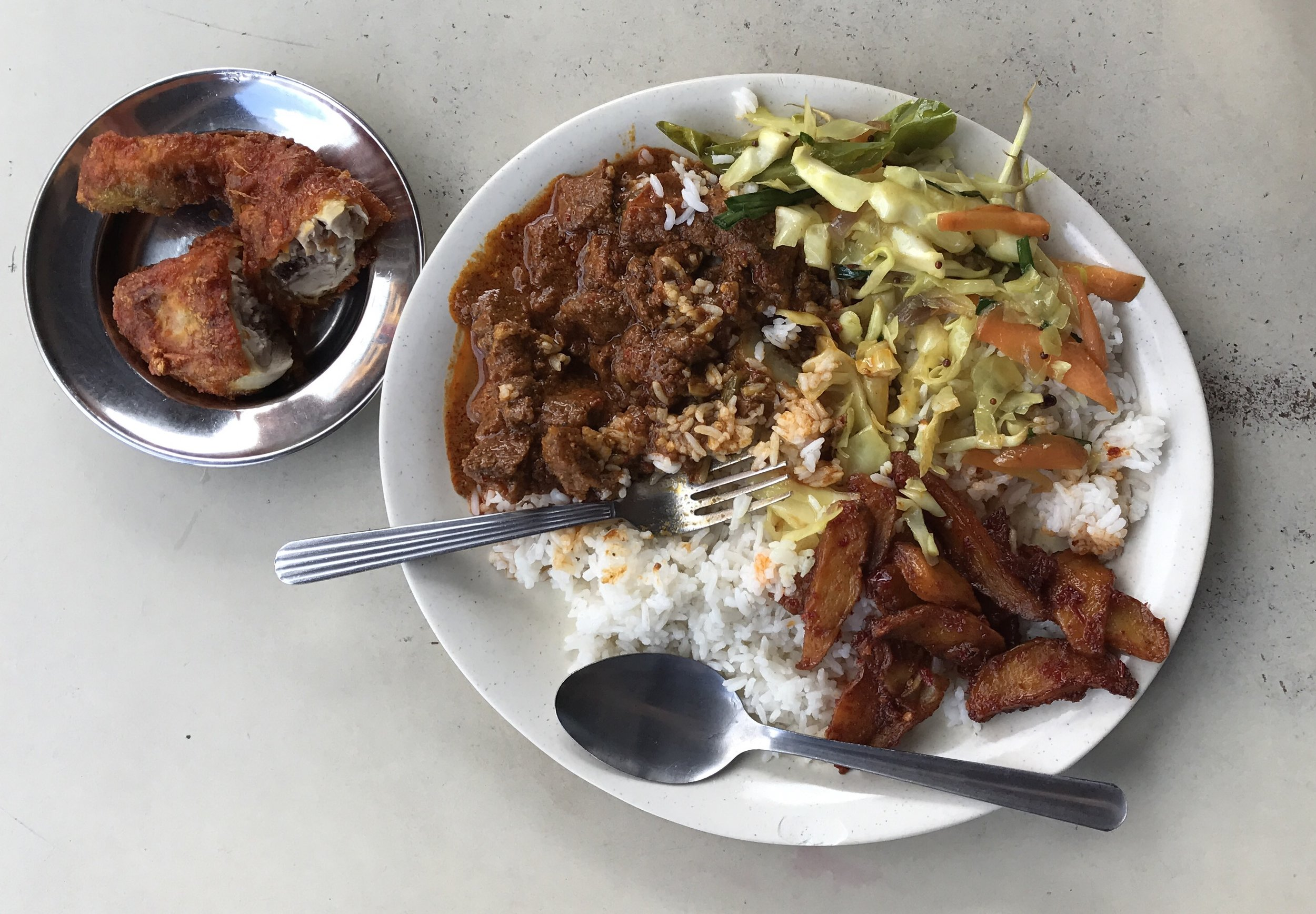 Beef curry, fried chicken, mixed greens, and potatoes in a spicy curry on top of rice - $1.