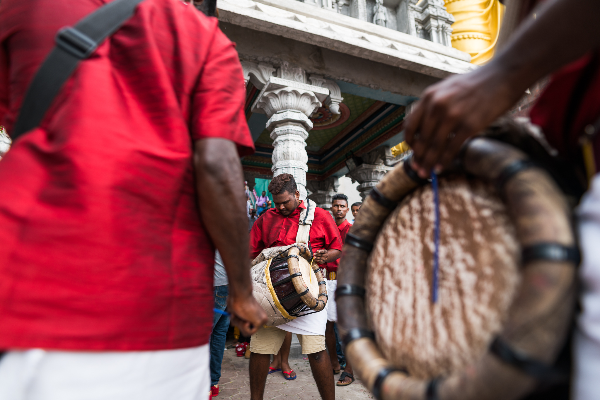 A drum circle forms around the man with the pierced back