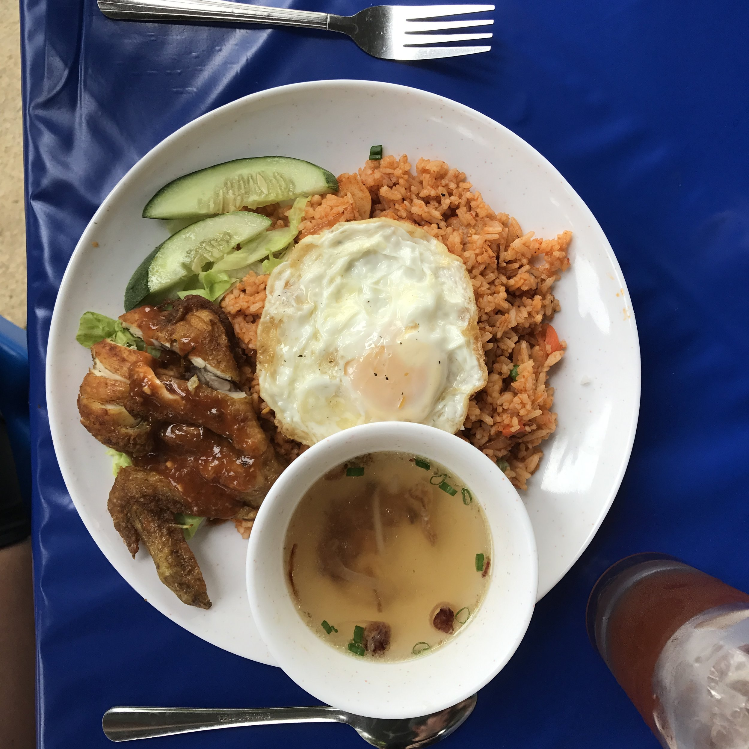 Simple roadside meals - chicken, rice, and a fried egg.