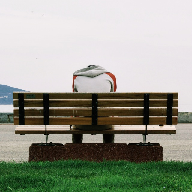 Man with head down on park bench