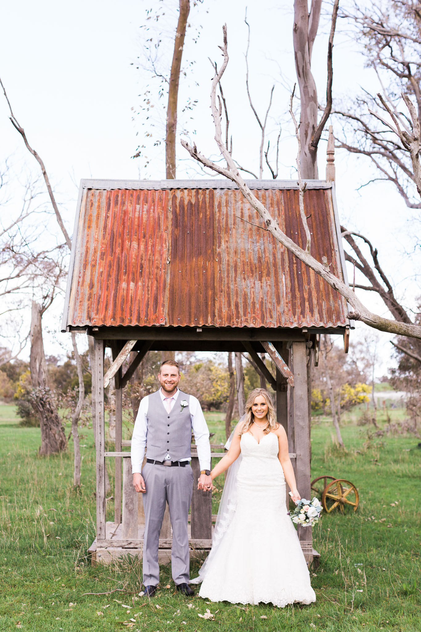 Bride and Groom Standing in front of old farm equipment - Gold Creek Station Wedding Photography