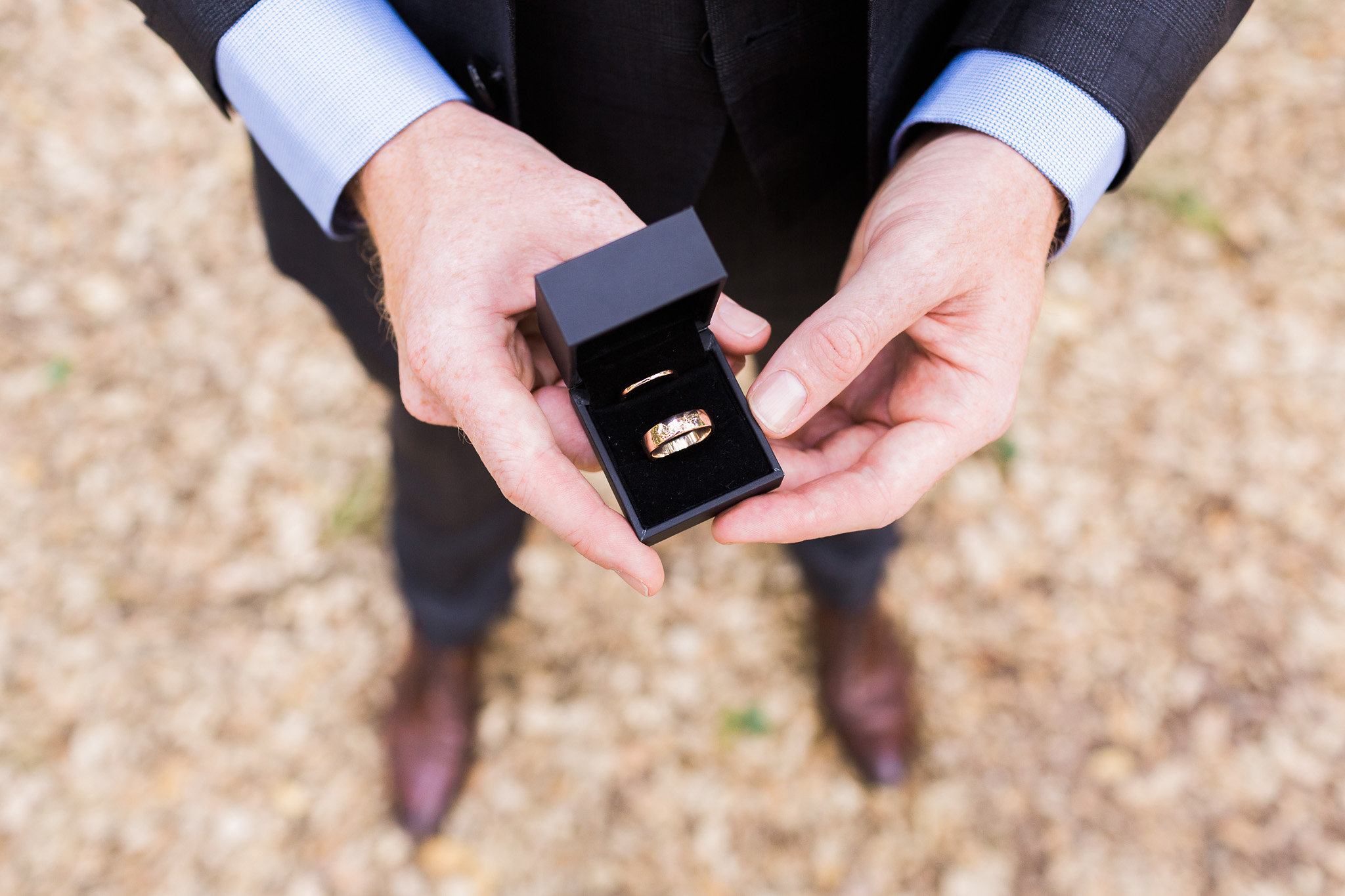 Groom holding the wedding rings in the Cork Forest, Canberra.
