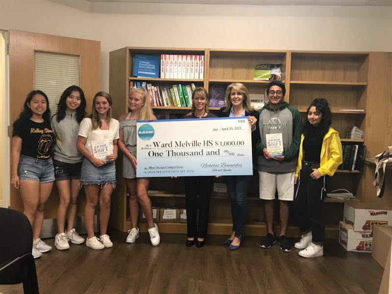 Professor Mauborgne presenting a $1k prize to Business Teacher Ilene Littman and her students at Ward Melville High School in East Setauket, New York.
